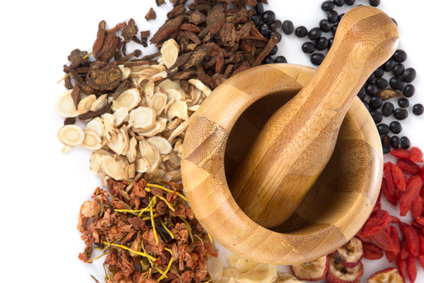 Wooden mortar & pestle surrounded by medicinal herbs